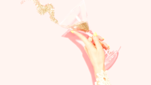 Person holding clear martini glass filled with glitter