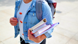 Woman wearing blue denim jacket holding books