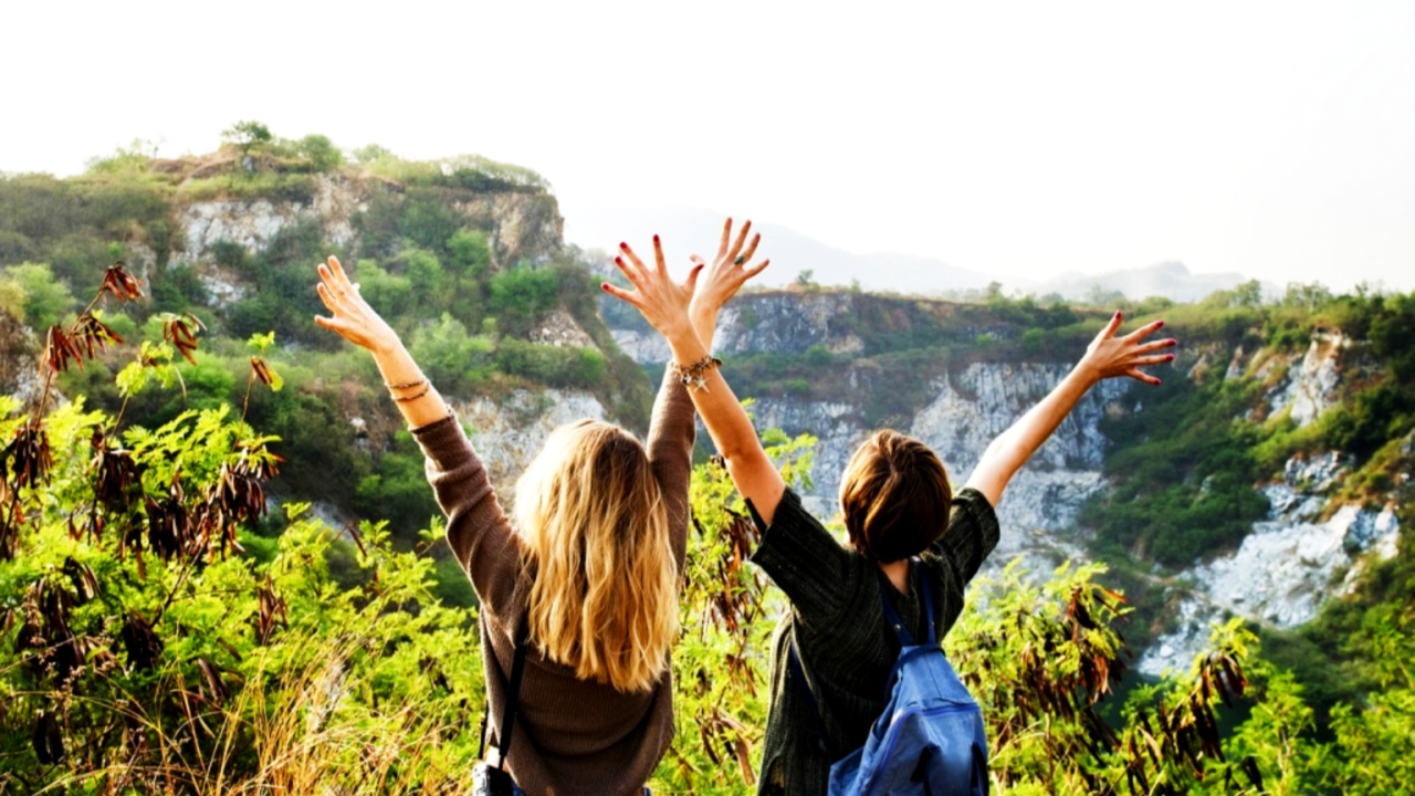 Two women in front of a mountain throwing their hands in the air