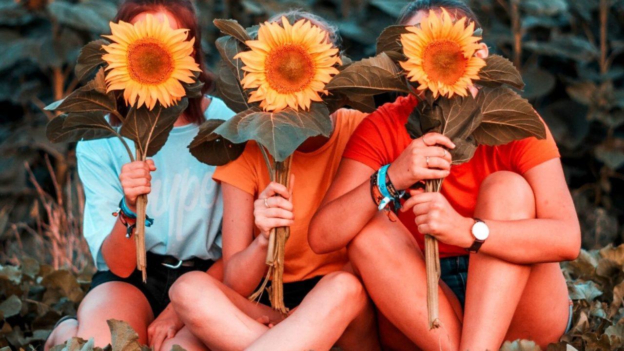 Three women holding sunflowers