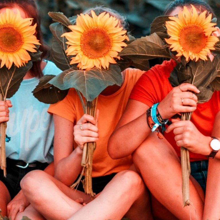 Three women holding sunflowers