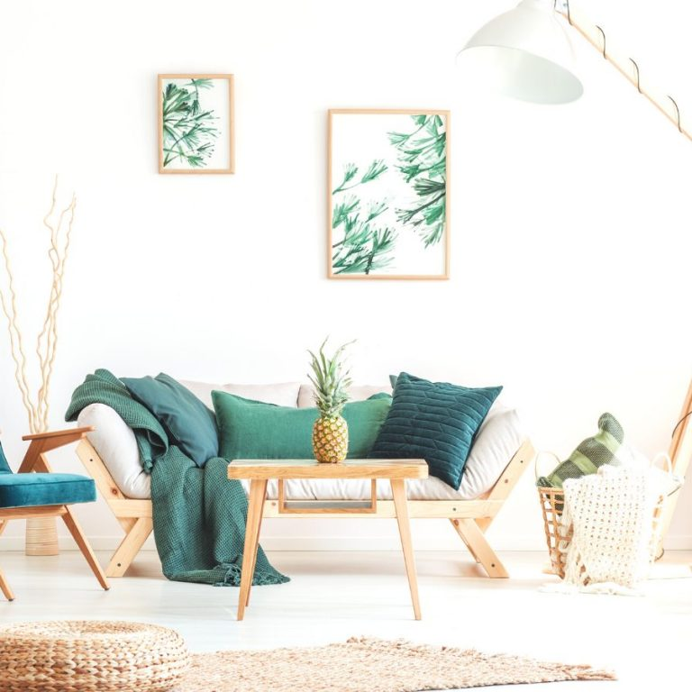 Pineapple on wood stool in living room with green furniture and braided pouf on carpet
